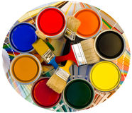 Different color cans of paint and brushes on swatches background. Stock Photography