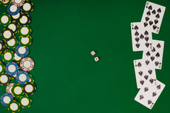 Different color chips for gamblings and playing cards on green Royalty Free Stock Image
