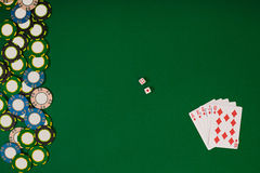 Different color chips for gamblings and playing cards on green Royalty Free Stock Photos