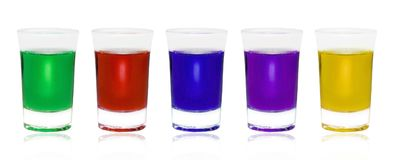 Different color drinks in glasses on white background. Five glasses with some colored liquid and one is different. Glass with green absinthe. Set a small shot stock images
