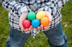 Egg hunt. Different color Easter Eggs in a child's hands- egg hunt stock image
