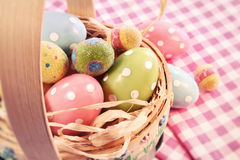 Different color eggs in a easter basket Stock Photos