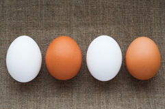 Different color eggs in line on hessian linen Royalty Free Stock Image