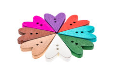 Different color heart shaped sewing buttons in a flower shape. Stock Photos