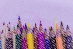 Different color pencils with white background. Covered by a white net Royalty Free Stock Photo