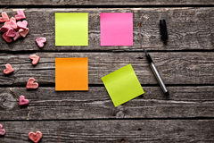 Different color sticky notes on wood table. Royalty Free Stock Image