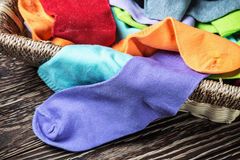 Different color textile socks in the basket Royalty Free Stock Photography