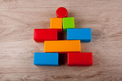 Different color toy blocks lay on wooden table Stock Photography