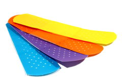 Different Colored Bandages. Blue, purple, orange, and yellow bandages sitting on an isolated background Stock Images