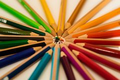 Cololed pencils lying in a circle royalty free stock photography