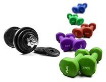 Different colored dumbbells on white Stock Images