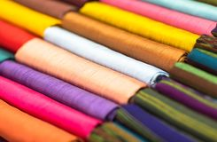 Different colored fabrics neatly folded for display. Closeup. stock images