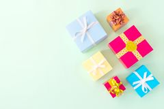 Different colored gift box on pastel light green background. Top. View of various present boxes on minimal background. Birthday, Christmas, wedding, valentine royalty free stock image