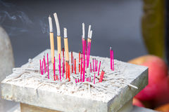 Different colored incentive sticks. Burning down on a small altar with a fruit background in a Chinese temple Royalty Free Stock Images