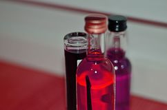 Different colored liquids in different bottles put together. One has a birch branch. Red, pink, purple Stock Photo