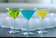 Different colored martinis with candles Royalty Free Stock Photography