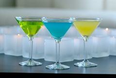 Different colored martinis with candles Royalty Free Stock Images