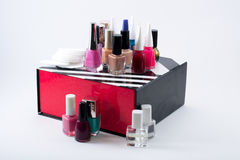 Different colored nail polish and cotton pads on a black/white/red box Stock Photos