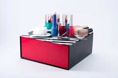Different colored nail polish and cotton pads on a black/white/red box Royalty Free Stock Photos