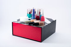 Different colored nail polish and cotton pads on a black/white/red box Stock Images