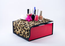 Different colored nail polish on a leopard cloth and black/white/red box Stock Images