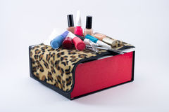 Different colored nail polish on a leopard cloth and black/white/red box. In a white background Stock Photo