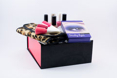 Different colored nail polish on a leopard cloth and black/white/red box. Smoky eyes ocean blue make up box in a white background Stock Photo