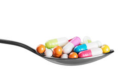 Different colored pill on a spoon Stock Photography