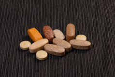 Pills. Different colored pills on a dark background Stock Photos