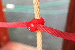 Different colored ropes with plastic fastenings on the playground. Different colored ropes with plastic fastenings on the children playground stock images