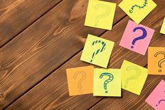 Different colored stickers with questions on wooden background. Concept of idea development royalty free stock photos