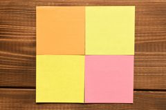 Different colored stickers on a wooden background. Empty text space.  stock photography