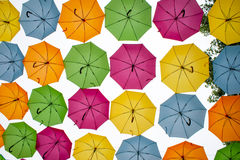 different colored umbrellas hanging in the air. Stock Photos