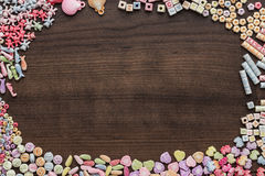 Different colorful beads on the wooden table Stock Photography