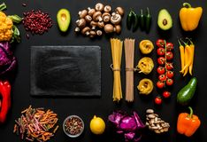 Different colorful Fresh raw ingredients for healthy vegetarian cooking on a black background with blackboard and free. Copy space. Flat lay, top view Royalty Free Stock Photos