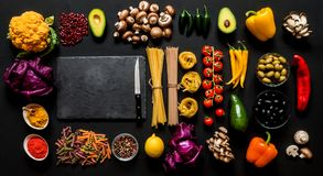Different colorful Fresh raw ingredients for healthy vegetarian cooking on a black background with blackboard and free. Copy space. Flat lay, top view Stock Photos