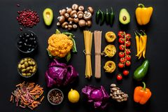 Different colorful Fresh raw ingredients for healthy vegetarian cooking on a black background. Flat lay, top view. Different colorful Fresh raw ingredients for Royalty Free Stock Photography