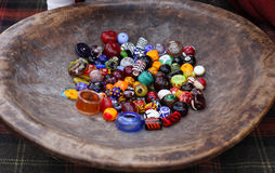 Different colorful glass beads on vintage wooden plate Stock Images