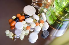 Different colorful pills and medicines. On a black mirror surface, close up, blur background Royalty Free Stock Images