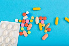 Different colorful pills and plastic packs - blisters stacked on blue abackground stock photography