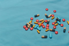 Different Colorful Pills, Tablets And Capsules On Blue Background Stock Photos