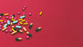 Different Colorful Pills, Tablets And Capsules On Red Background Stock Images