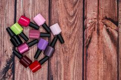 Different colorful small nail polish bottles. On wooden desk stock images