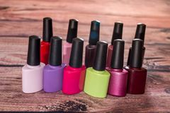 Different colorful small nail polish bottles. On wooden desk stock image