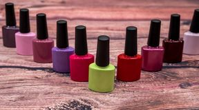 Different colorful small nail polish bottles on wooden royalty free stock images