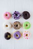Different colorful sweet donuts. On white painted wood background royalty free stock photos