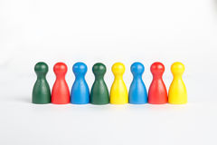 Different colors of game figurines in a line Stock Image