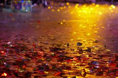 Different colors of holiday. Shining confetti on a stage are shined by projectors of different colors on a holiday Stock Photos