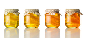 Different Colors of Honey in Jar on White Background Stock Photos