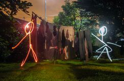 Male and Female, working together, drawn by lights. The different colors of light separate the male and female cartoon stick figures drawn at night with an open stock images